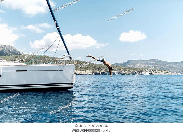 Man jumping from his sailing boat into the sea