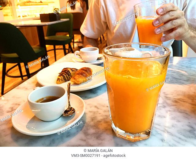 Breakfast in a cafe: two cups of coffee, two orange juices and cakes. Spain