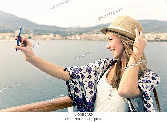 Smiling woman on cruise liner taking selfie with smartphone