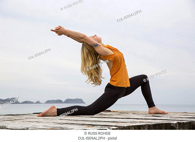 Mid adult woman bending backwards practicing yoga on wooden sea pier