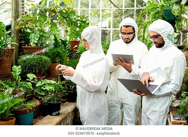 Scientists using technologies while examining plants
