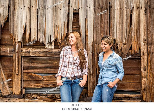 Two young women standing outside barn, smiling
