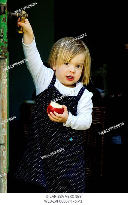 Germany, Portrait of girl eating apple