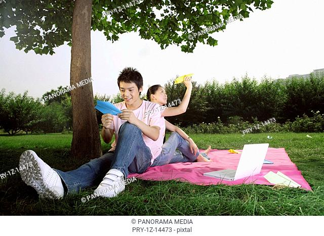 Young couple sitting under tree and holding paper airplane