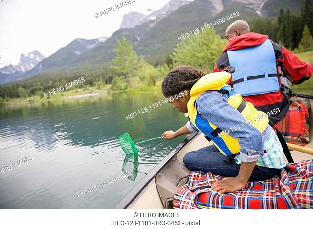 Father and daughter fishing in canoe on lake
