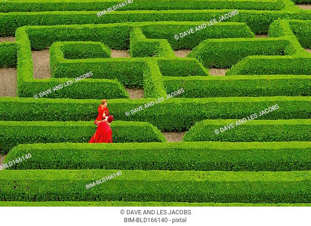 Aerial view of Caucasian couple in medieval costumes walking in hedge maze