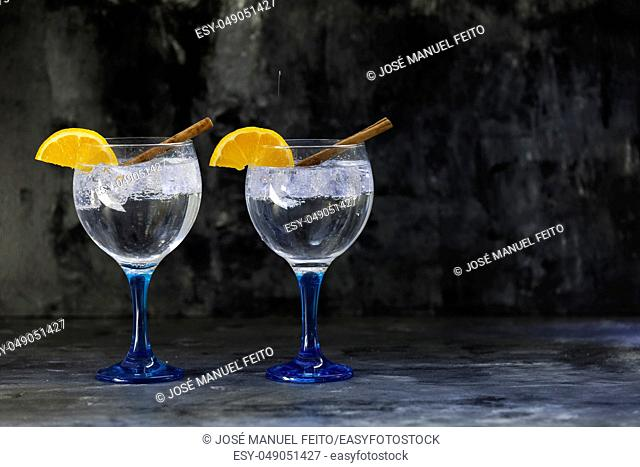 two gin tonics on blue glass with orange slice and cinnamon sticks on dark backdrop