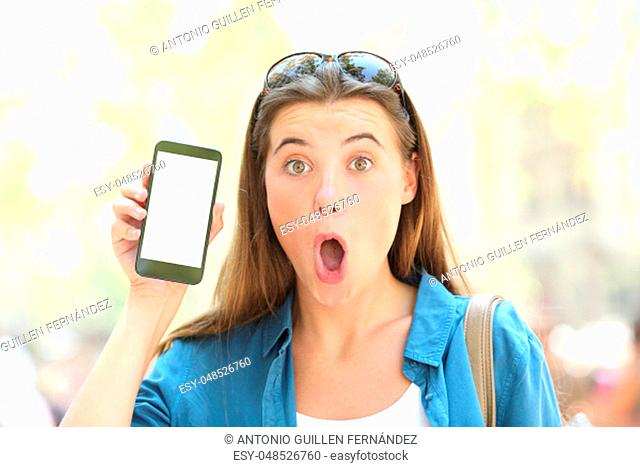 Front view portrait of a surprised girl showing a blank smart phone screen outdoors in the street