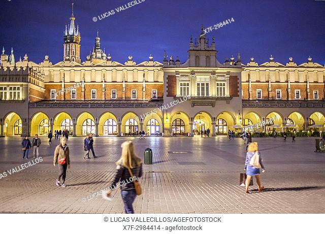 The Cloth Hall, in background St Mary the Virgin Basilica, at Main Market Square at dusk, Krakow, Poland