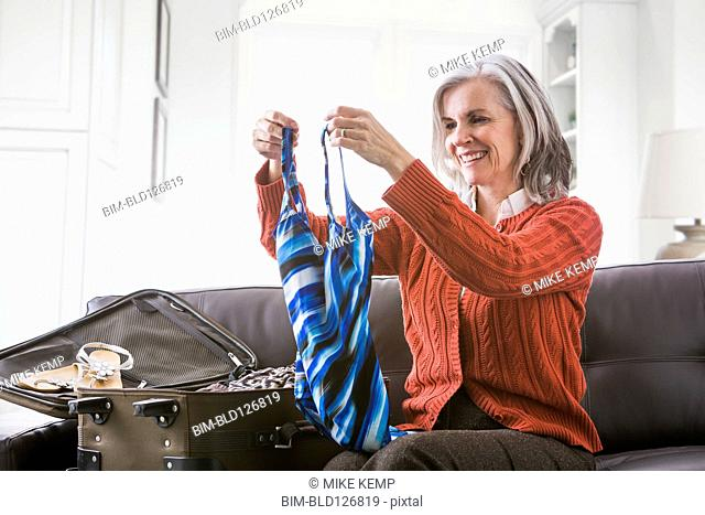 Caucasian woman packing bathing suit in suitcase