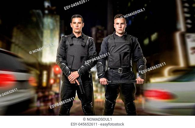Two cops with a gun and a baton on the guard of the law, concept. Special force troops in black body armor, front view, night cityscape on background