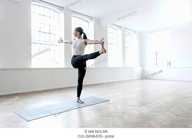Woman in dance studio leg raised, stretching