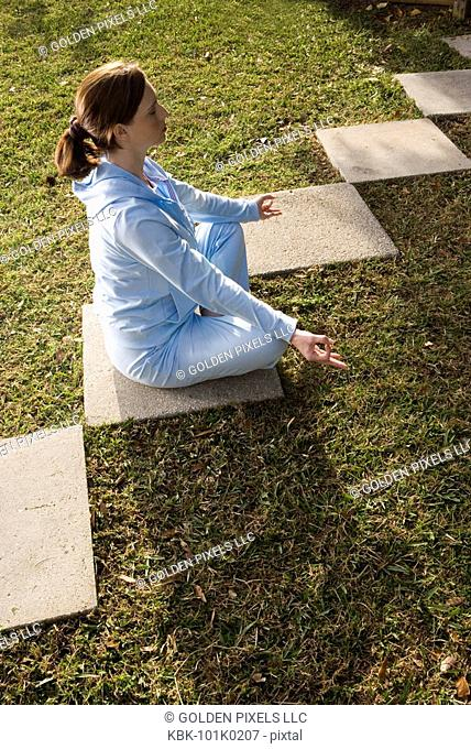 Portrait of a young woman sitting on a stepping stone in a yoga position