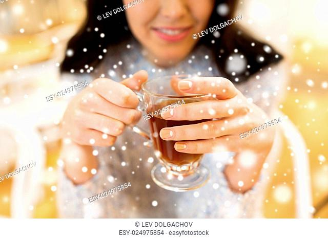 leisure, drinks, people and lifestyle concept - close up of happy young woman drinking tea at cafe