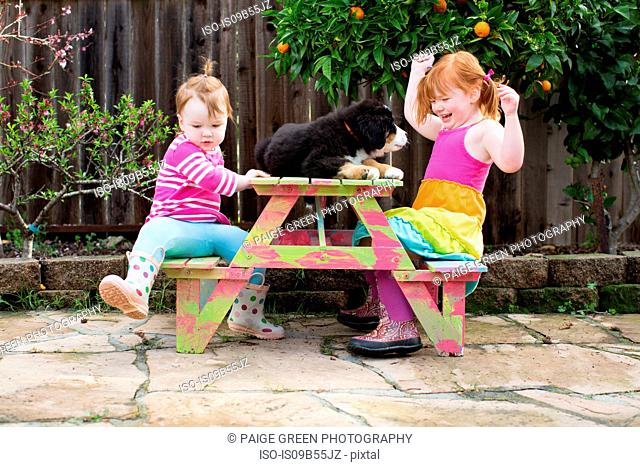 Two young sisters sitting on garden bench with pet dog