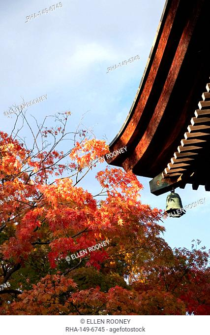 Bright orange acer leaves next to a bell and the wooden roof of the Hida Kakubun-ji Pagoda in Takayama, Japan, Asia