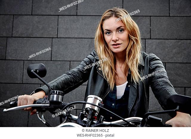 Portrait of confident young woman on motorcycle