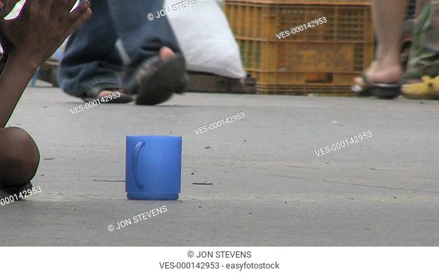 Eine Person sitzt am Strassenrand und bettelt