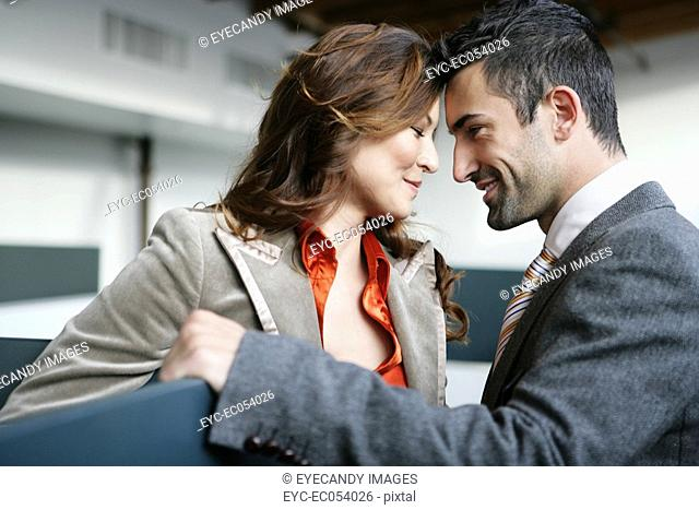 Two people smiling at each other in the office