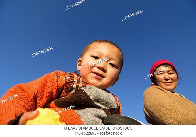 little boy with an apple in Bayan-Ölgii in Western Mongolia