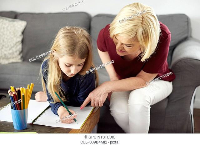 Grandmother helping granddaughter with colouring at home