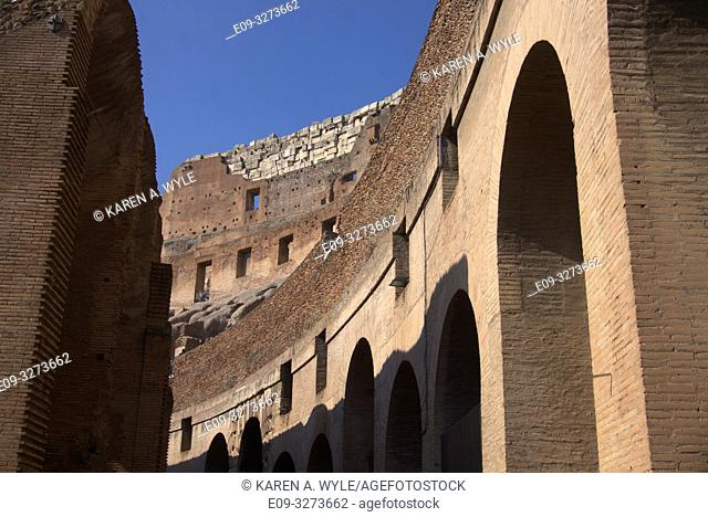 inside of Colosseum, including rebuilt section of wall, on sunny day with blue sky, Rome, Italy