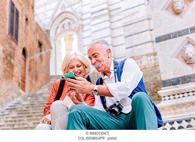 Tourist couple looking at smartphone on Siena cathedral stairway, Tuscany, Italy