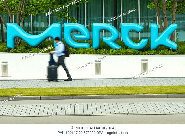 14 June 2019, Hessen, Darmstadt: A man walks past the lettering of the Darmstadt-based chemical and pharmaceutical company