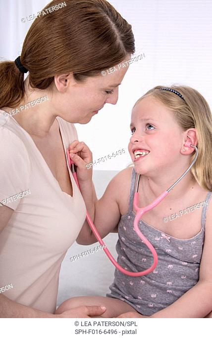 MODEL RELEASED. Girl using stethoscope with mother