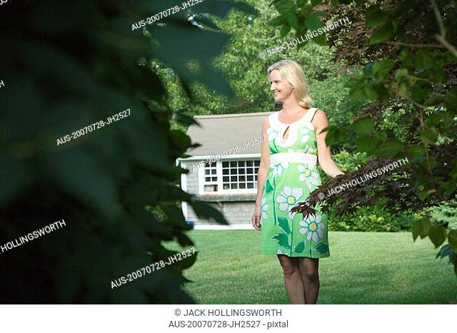 Mid adult woman standing in a lawn and smiling