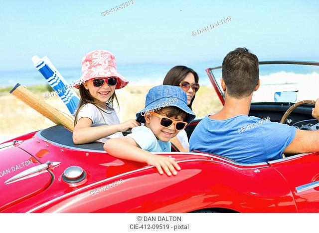 Family riding in convertible at beach