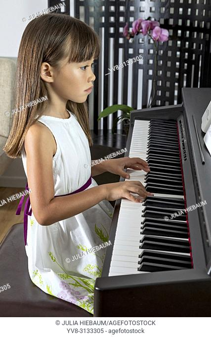 Six year old girl practicing her piano