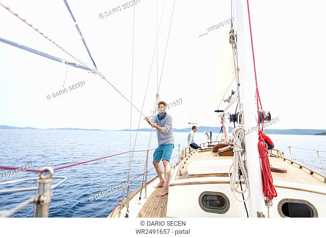 Man pulling on rope on sailboat