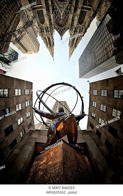 Low angle view of Atlas and Globe outside the Rockefeller Center, Rockefeller Plaza, Manhattan, New York, USA. St. Patrick's Cathedral and skyscrapers