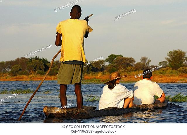 Poler with tourists in a traditional mokoro logboat on excursion in the Okavango Delta, Botswana