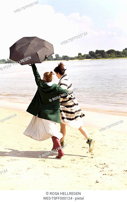 Back view of two friends running side by side on the beach with an umbrella