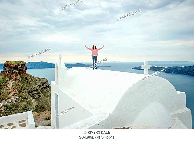 Girl standing on top of church, Oía, Santorini, Kikladhes, Greece