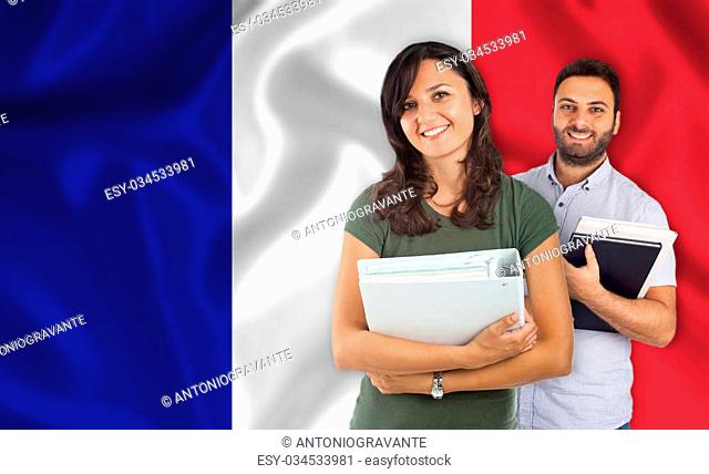 Couple of young students with books over french flag