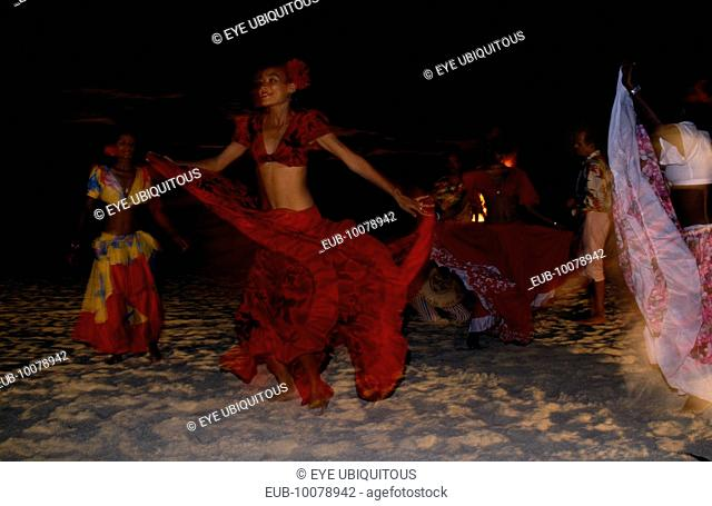 Women in red costume dancing on the beach at night. Sega is the national dance and music form of Mauritius