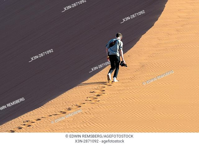 A tourist begins ascending Dune 45, an ancient dune in the Soussuvlei salt pan in Namib-Naukluft National Park, located in Namibia, Africa