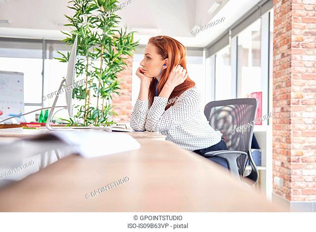 Woman sitting at desk looking away