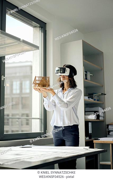 Woman holding architectural model of house, using VR glasses
