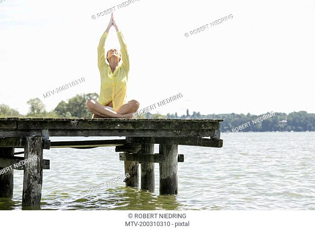 Woman doing lotus pose yoga on jetty at the lake, Ammersee, Upper Bavaria, Germany