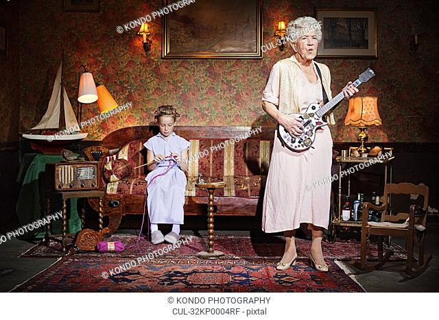 Older woman playing guitar as girl knits