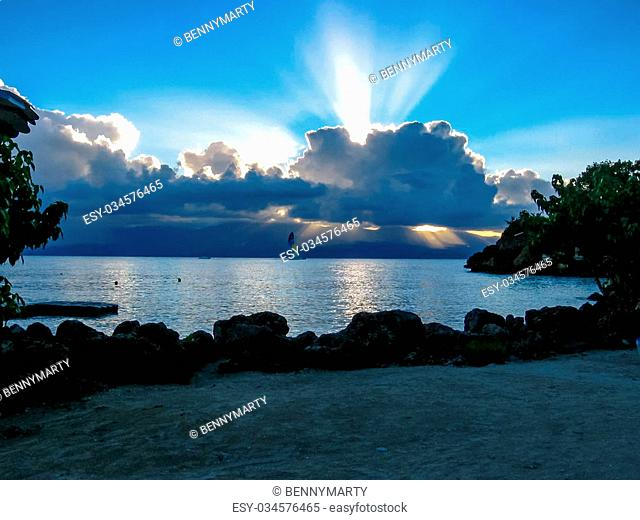 Tropical landscape of Guadalupe in the French Caribbean in the summer at sunset with low clouds in the sky over the sea