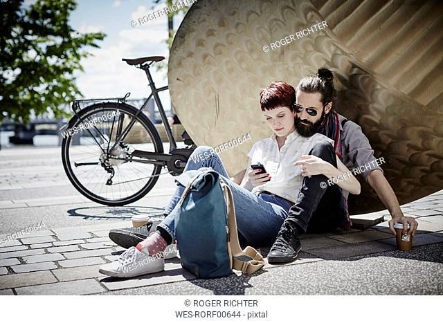 Germany, Hamburg, couple on bicycle trip having a rest looking at cell phone