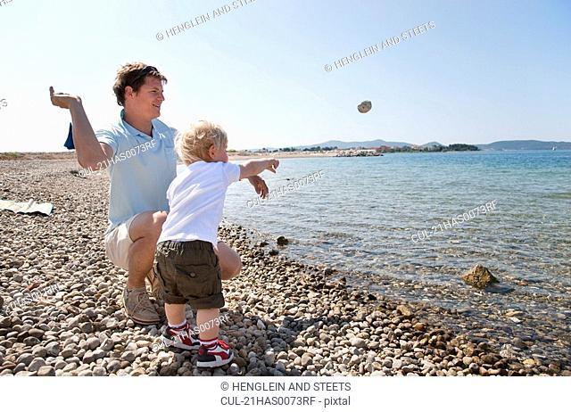 Father and son throw stones at beach