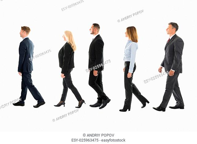 Full length side view of business people walking against white background