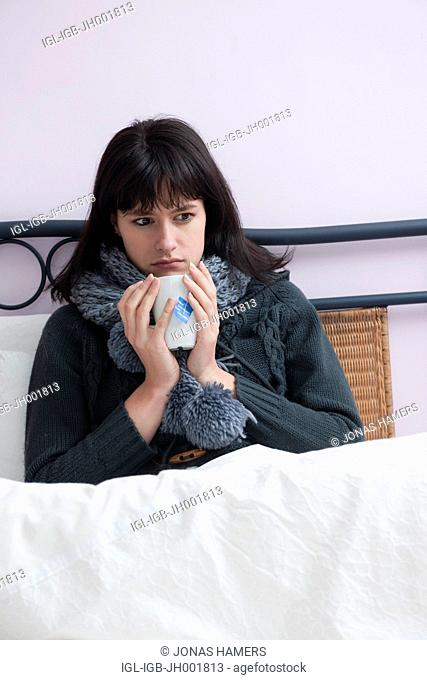 This picture shows a young caucasian woman with brown hair as she lies in her bed feeling ill or sick drinking a warm beverage in a cup