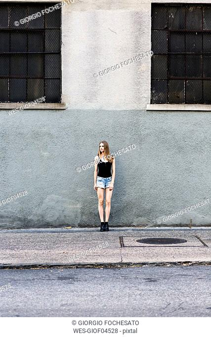 Young woman standing in front of building, waiting